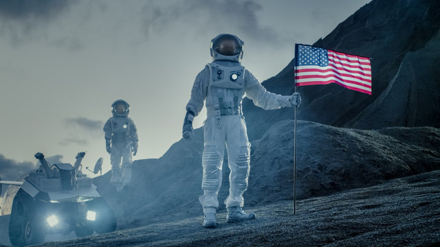 Two Proud Astronauts Plant American Flag on the Alien Planet. In the Background Research Base and Rover.