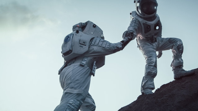 Two Astronauts Climbing Mountain Hill Helping Each Other, Reaching the Top. Overcoming Difficulties, Important Moment for the Human Race.