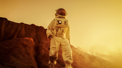 Brave Astronaut Descents from the Mountain on the Alien Red Planet/ Mars. Space Exploration/ Travel, Colonization Concept.
