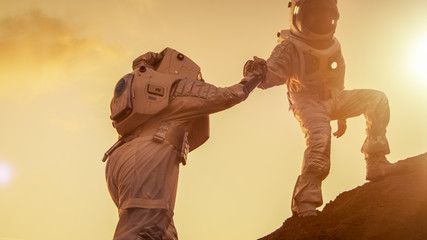 Two Astronauts Climbing Mountain Hill Helping Each Other, Reaching the Top. Helping Hand. Overcoming Difficulties, Important Moment for the Human Race.