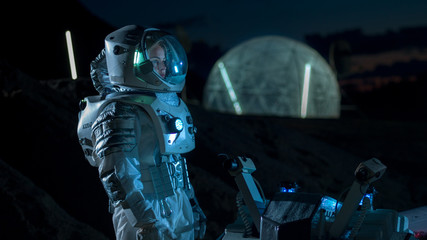 Astronaut Looking Around while Standing near Rover on the Alien Planet at Night. In the Background His Base/ Research Station. Space Exploration, Colonization Theme.