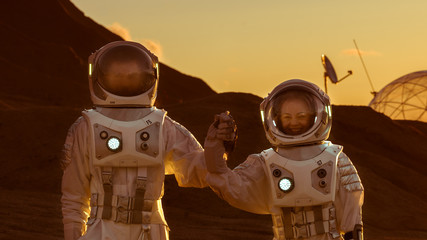 Two Astronauts Wearing Space Suits Holding Hands on Mars/ Red Planet. Love in Space Travel, Exploration and Colonization Concept.