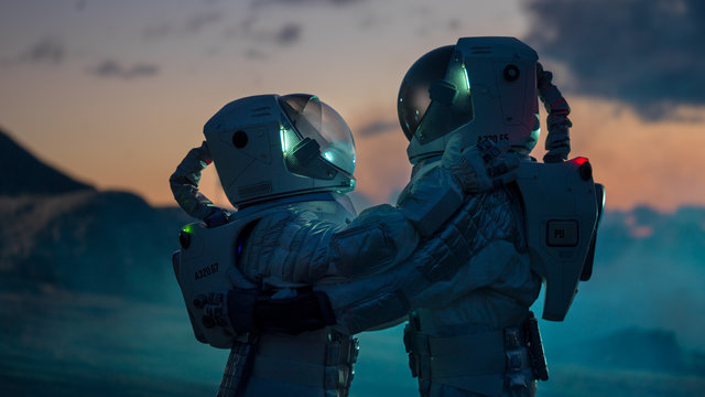 Two Astronauts in Space Suits Hugging on Alien Planet, Exploration of the the Planet's Surface. Love in Space Travel Concept.