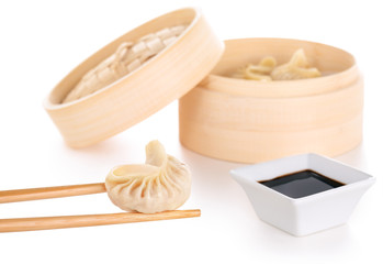 chopsticks holding a chinese dumpling, soy sauce and bamboo basket in white background