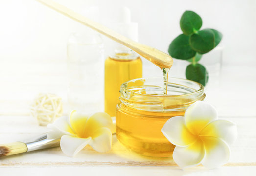 Honey spa treatment. Pouring sweet golden honey to jar, plumeria flowers, soft sunny light. Natural homemade skincare.