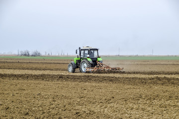Lush and loosen the soil on the field before sowing. The tractor plows a field with a plow