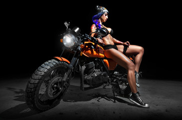 Stylish motorcycle chopper with sexy tattoed chick rider at night