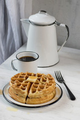 stack of thick waffles with butter and syrup with black and white enamel dishes on white table