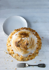 lemon meringue pie on white table with fork and crumbs top view