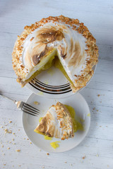 cut lemon meringue pie with thick slice on white plate on white table with fork and crumbs top view