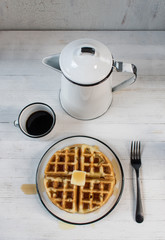 stack of thick waffles with butter and syrup with black and white enamel dishes on white table top view