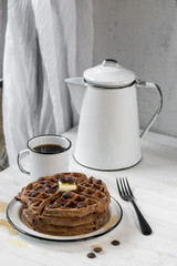 stack of thick chocolate waffles with chocolate chips, butter, and syrup with black and white enamel dishes on white table