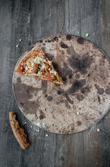 last slice pepperoni pizza on dark gray wood table top view
