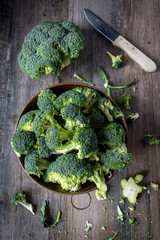 fresh cut broccoli florets in copper bowl in rustic farmhouse setting top view