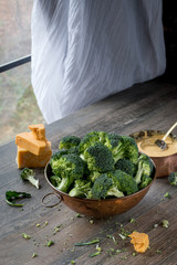 fresh cut broccoli florets in copper bowl with cheese sauce and ingredients in rustic farmhouse setting