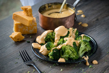 steamed broccoli florets on plate covered in cheese sauce in rustic farmhouse setting