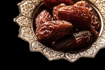 Close-up portrait of dates which are a traditional food to break fast during the holy month of ramadan on a silver serving platter with a black background. Dubai, UAE.
