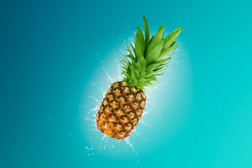 Water splashing out of a fresh pineapple isolated on blue background\