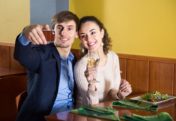 young couple pictures of yourself on your smartphone for dinner in a restaurant