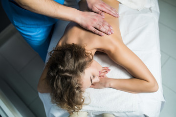 Top view of woman receiving back massage at spa. Female having relaxing massage on her back in spa.