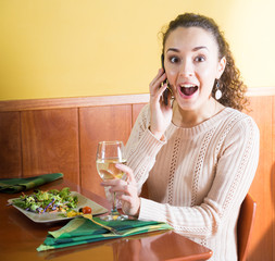 young woman talking on phone surprised at dinner in restaurant