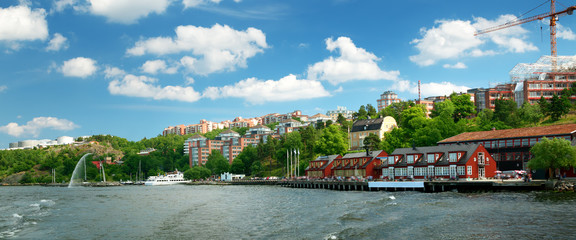 View to Stockholm, Sweden with a ferry from sea in summer. Nacka strand houses and harbour on sunny day