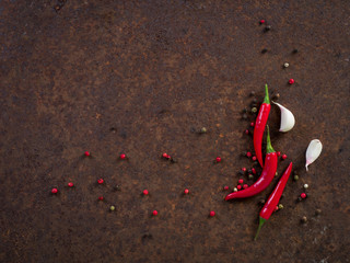 red hot chili pepper pods and peas, garlic clove on dark rusty metal background, top view, copy space