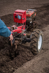 Farmer plows the land with a cultivator, preparing it for planting vegetables