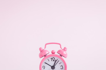 Small alarm clock on rose background