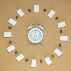 Alarm clock with coffee beans and sugar cubes. Minimalistic hot sweet drink concept
