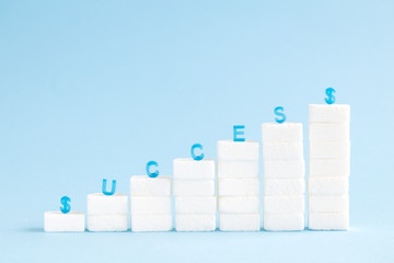 Business growth chart made of sugar cubes with success letters isolated on blue minimalistic creative concept.