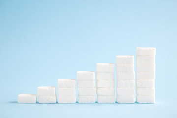 Business growth chart made of sugar cubes isolated on blue minimalistic creative concept.