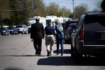 Federal agents walk down Mission Oaks Boulevard following an explosion in Austin