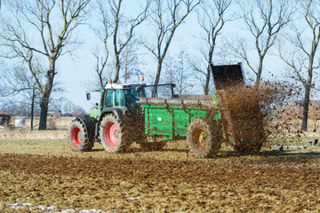 Tractor with manure spreader on the field - 1408