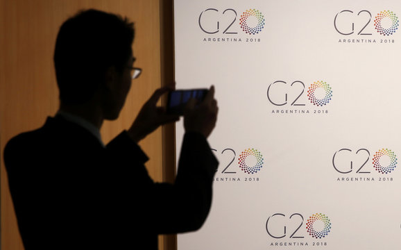 A man takes pictures of a board with the G20 Meeting of Finance Ministers logo in Buenos Aires