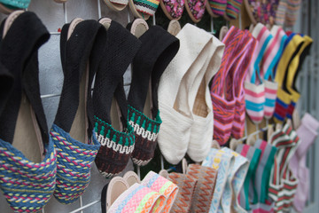 Handmade footwear. Handcraft colorful slippers on sale. Latin American artisans colorful crafted slippers hanged on the wall.