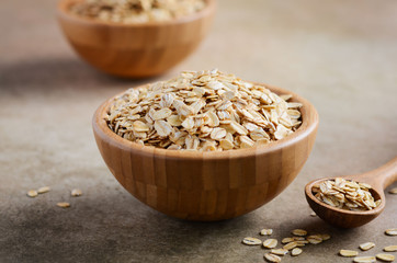 Oat flakes in a wooden bowl and wooden spoon on light brown background, selective focus.