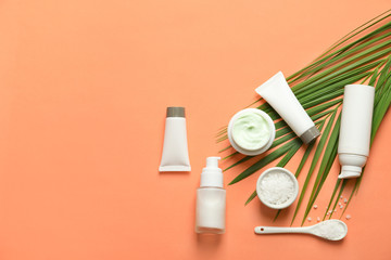 Different skin care cosmetic products with green leaf on color background, top view