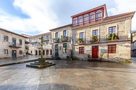 Spanien - Historischer Platz Praza da Lena in Pontevedra in Galicien. Gebäude mit farbiger Fassade, Holzfenstern, Balkonen und einem Steinkreuz in der Mitte.