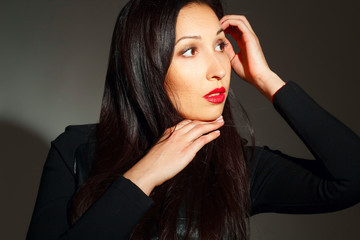 Portrait of young beautiful woman with red lipstick over dark background. Beauty portrait concept.