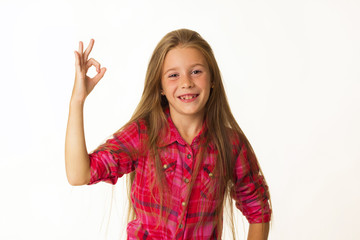 Young beautiful little girl smiles showing hand ok sign over white background