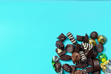chocolate assorted assorted lined with a slide in the lower right corner of the frame on a blue paper background, on the left there is space under the text