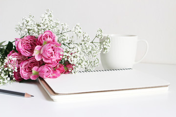 Styled stock photo. Closeup of wedding bouquet made of pink roses and baby's breath, Gypsophila flowers lying on white table. Feminine still life, blank notebook, pencil and white cup of coffee.