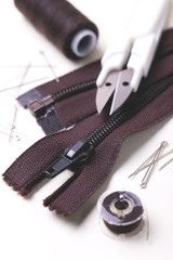Sewing pins, scissors, zipper and plastic bobbin with colour threads