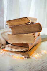 Stack of old vintage books lies on a light wooden table and next to it is a garland. Reading. Closeup.