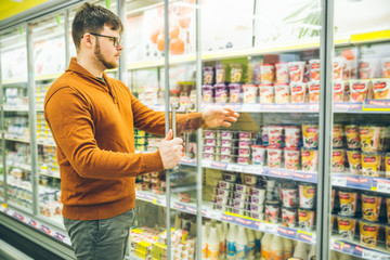 man takes yogurt from fridge. grocery shopping concept