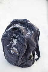 Snow-covered blue backpack with a water bottle in your pocket standing on a snowdrift, chilly overcast day.