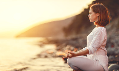 Fototapete - woman practices yoga and meditates in lotus position on sunset beach.