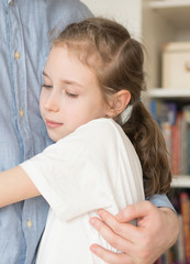 Cute little girl hugging her dad.