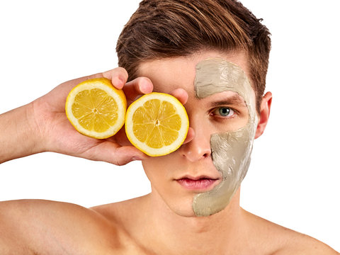 Facial mask from fresh fruits and clay for man concept. Face with treatment mud applied. Male holding lemon half for skin care procedure in salon. Acne Removal.